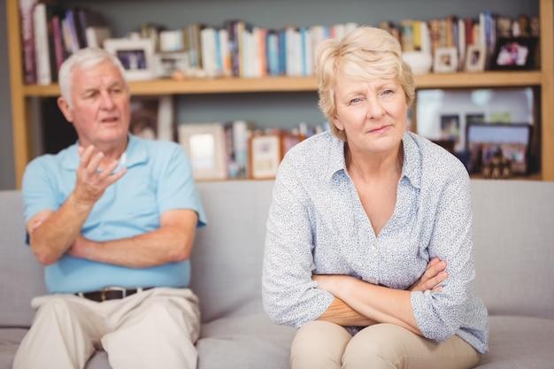Senior pareja discutiendo mientras está sentado en el sofá