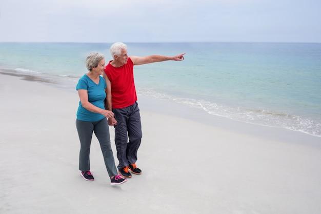 Senior pareja hablando y caminando por la playa