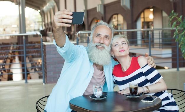 Senior pareja hace una selfie usando un teléfono en el café.