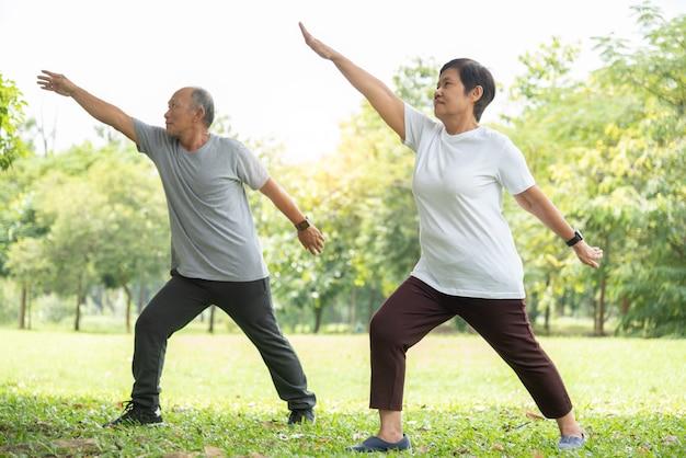 Senior pareja haciendo ejercicios de estiramiento en el parque.