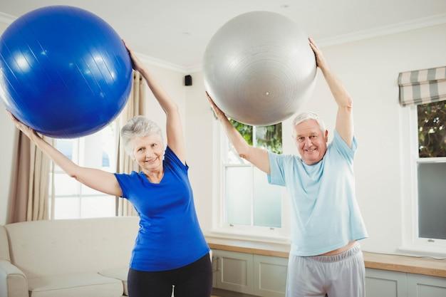 Senior pareja levantando la pelota de ejercicios mientras hace ejercicio