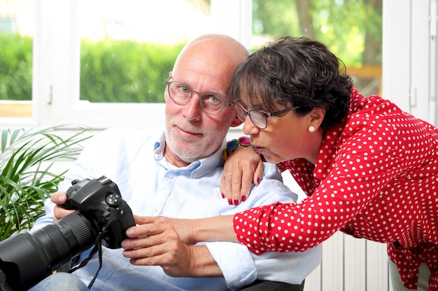 Senior pareja mirando fotos en la pantalla de la cámara