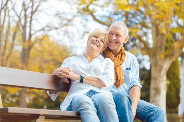 Senior pareja sentada en un banco en el parque otoño