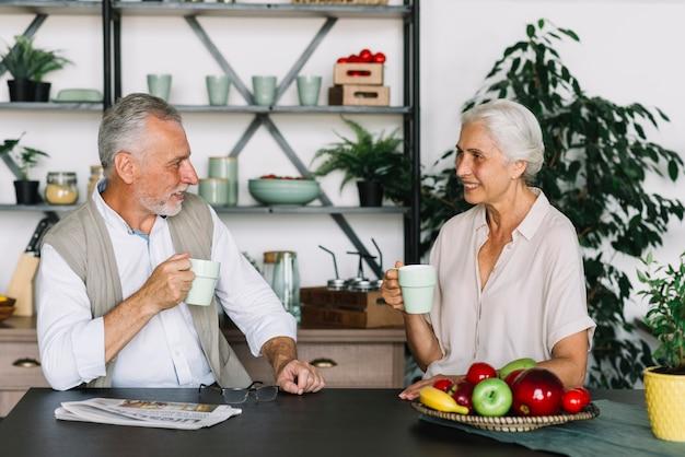 Senior pareja sentada en la cocina desayunando juntos