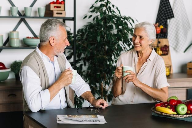 Senior pareja sentada en la cocina disfrutando del café