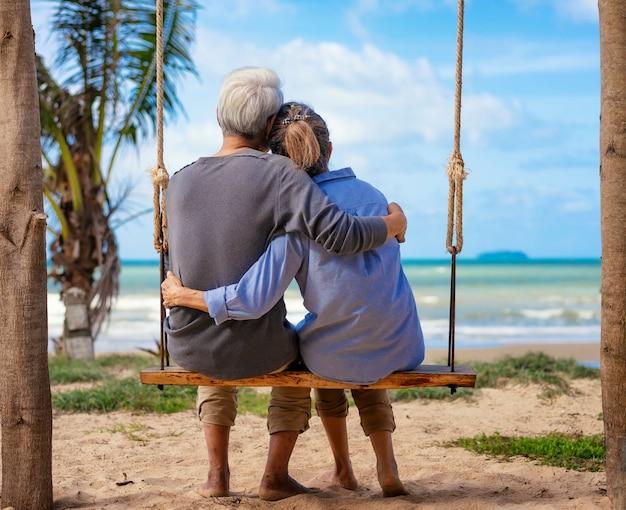 Senior pareja sentada en un columpio en la playa
