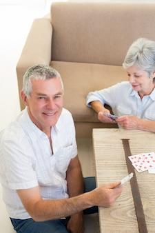 Senior pareja sentada en piso jugando a las cartas