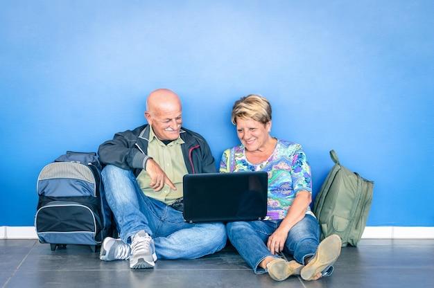 Senior pareja sentada en el piso con laptop esperando un vuelo en el aeropuerto