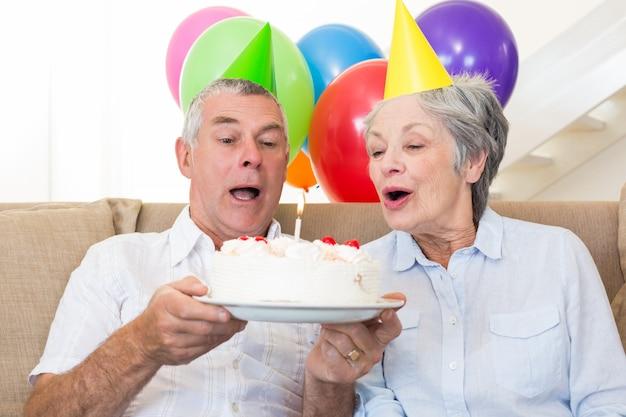 Senior pareja sentada en el sofá celebrando un cumpleaños
