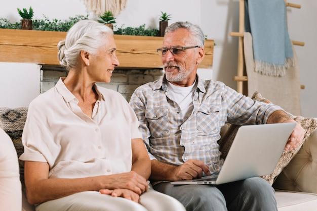 Senior pareja sentada en el sofá mirando el uno al otro