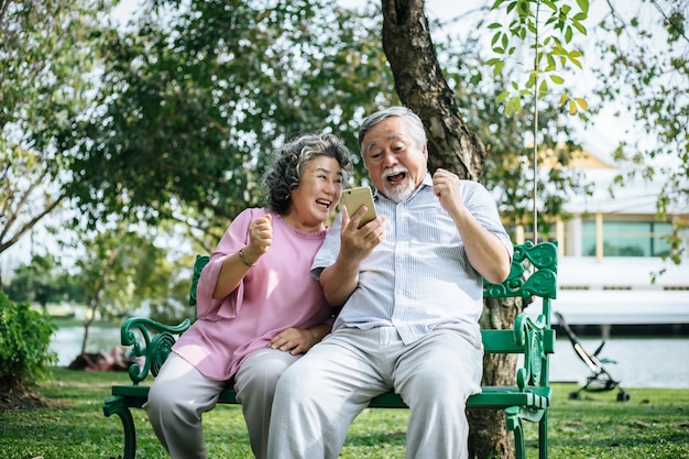 Senior pareja tomando una foto selfie con teléfono inteligente en un parque