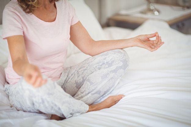 Senior practicando yoga en la cama