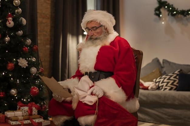 Senior santa leyendo una carta de navidad