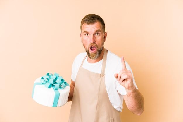 Senior sosteniendo un pastel aislado sobre fondo beige teniendo una idea, concepto de inspiración.