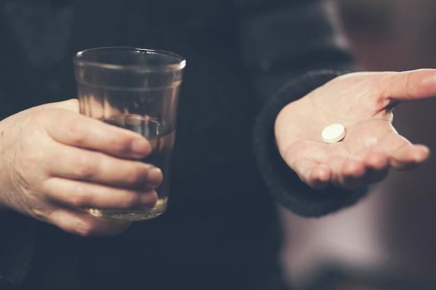 Senior sosteniendo una pastilla y un vaso de agua