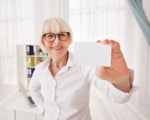 Senior sosteniendo una tarjeta de visita con espacio de copia