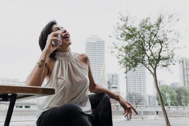 Senior sosteniendo un teléfono en el fondo de la ciudad