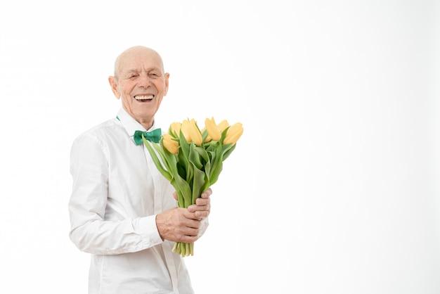 Senior tiene ramo de flores amarillas en manos