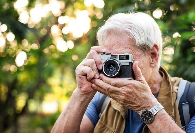 Senior trekker tomando una foto con una cámara de cine