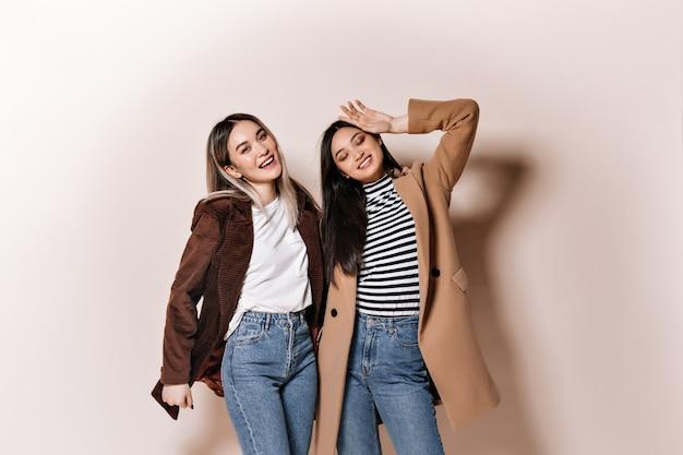 Señora en abrigo y su amiga en chaqueta riendo en pared aislada