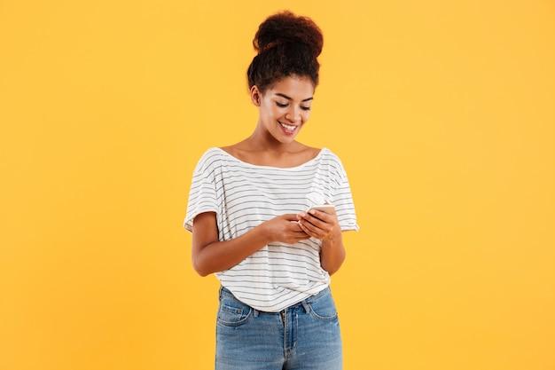 Señora africana alegre usando y escribiendo teléfono aislado