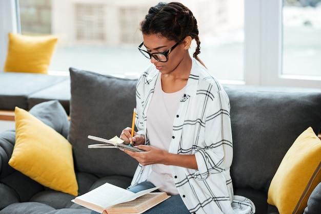Señora africana atractiva con gafas escribiendo notas.