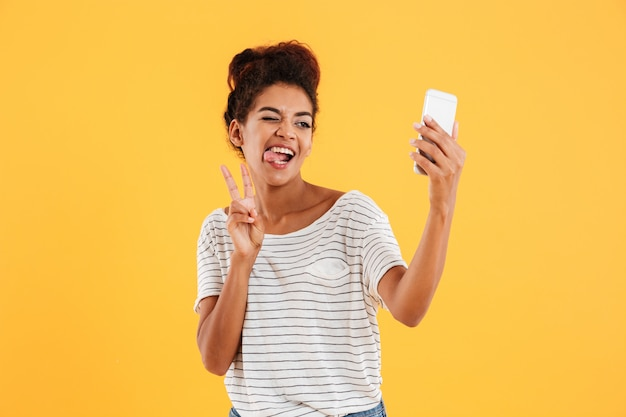 Señora africana divertida haciendo muecas y haciendo selfie en teléfono aislado