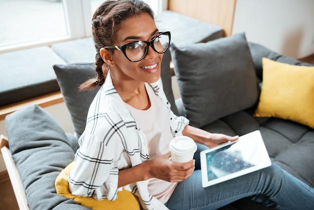 Señora africana feliz con gafas sentado en la biblioteca con tableta