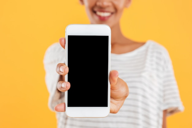 Señora africana feliz que muestra el teléfono con la pantalla en blanco aislada