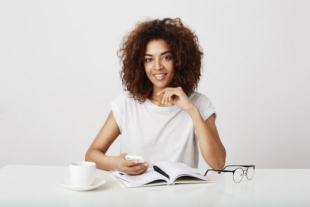 Señora africana del negocio que sonríe sosteniendo el teléfono que se sienta en el lugar de trabajo sobre la pared blanca. copia espacio