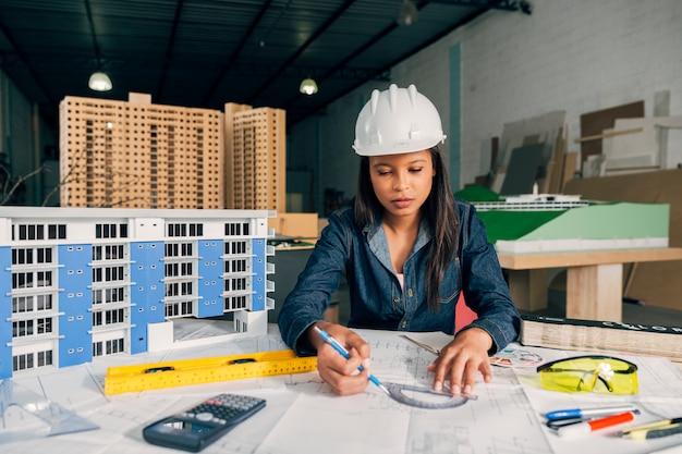 Señora afroamericana en casco de seguridad trabajando cerca de modelo de edificio