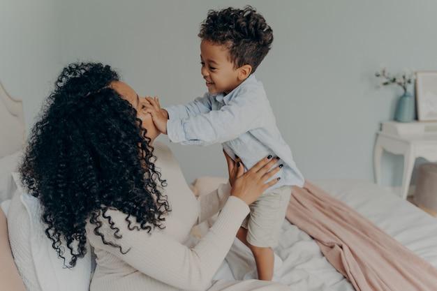 Señora afroamericana embarazada jugando con su hijo en casa