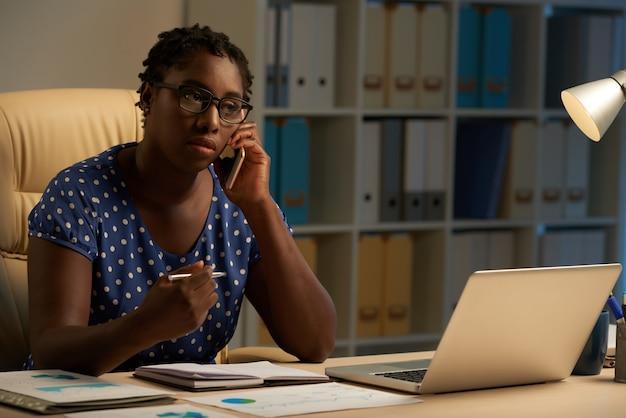 Señora afroamericana sentada en el escritorio en la oficina por la noche y hablando por teléfono móvil