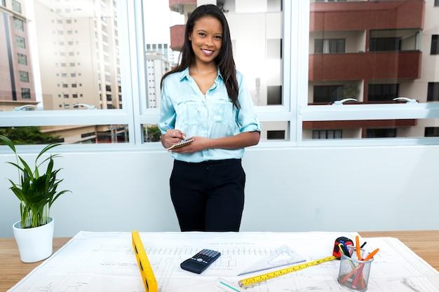Señora afroamericana sonriente que toma notas cerca del plan en la tabla con equipos