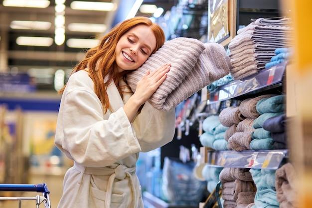 Señora en albornoz de compras, compra una toalla, disfrutando de la suavidad de la toalla nueva cerca de los estantes