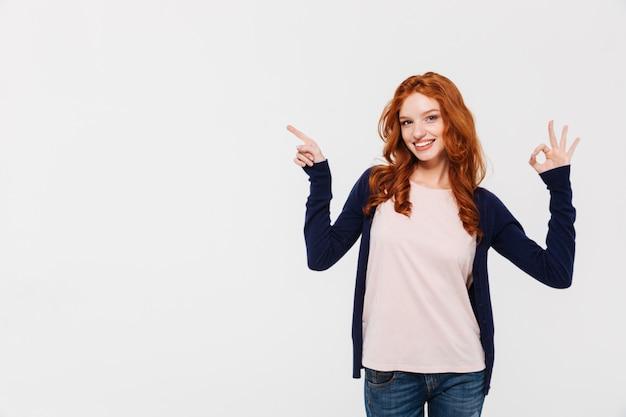 Señora alegre bastante joven del pelirrojo que muestra gesto aceptable mientras que señala.