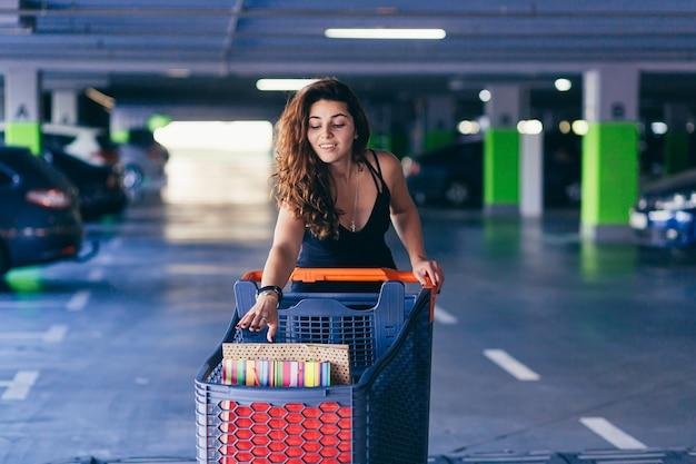 Señora alegre en elegante vestido negro llevando bolsas de colores en un estacionamiento cerca de un coche.
