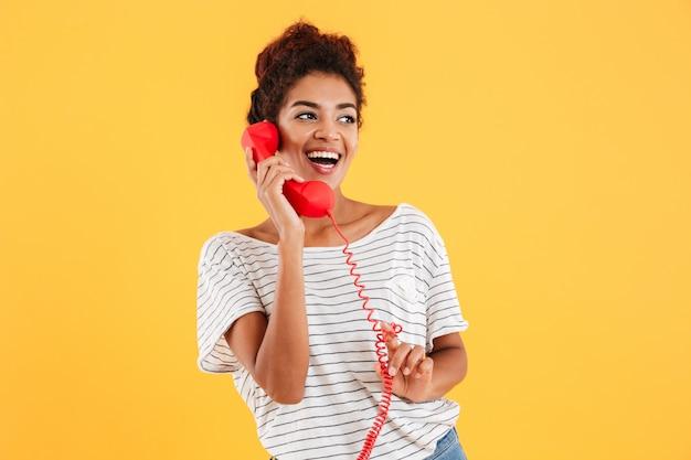 Señora alegre hablando por teléfono rojo y mirando a un lado