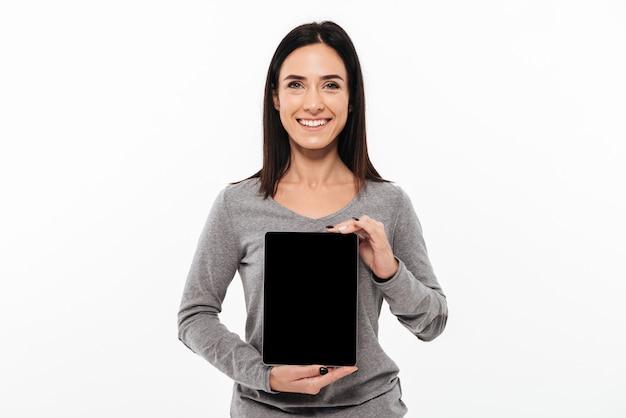 Señora alegre joven que muestra la exhibición de la tableta.