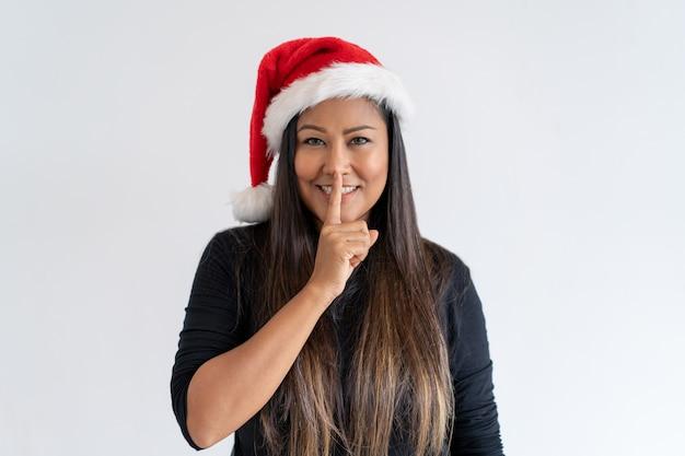 Señora alegre de la navidad que muestra shh gesto
