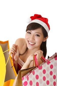 Señora alegre de la navidad que sostiene las bolsas de la compra y que sonríe, retrato del primer aislado en el fondo blanco.