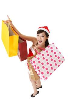 Señora alegre de navidad sosteniendo bolsas de la compra y sonriente, retrato de cuerpo entero aislado sobre fondo blanco.