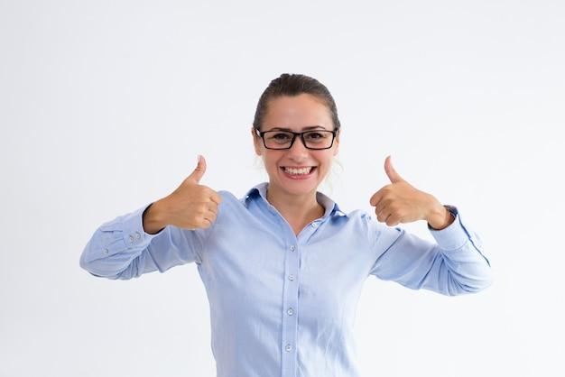 Señora alegre del negocio que muestra los pulgares para arriba y que mira la cámara