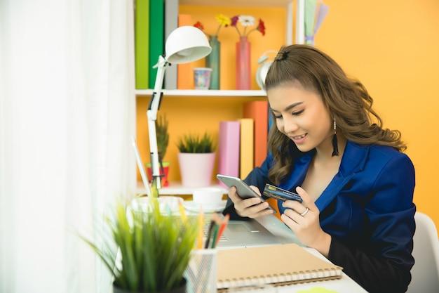 Señora alegre del negocio que trabaja en la computadora portátil en oficina