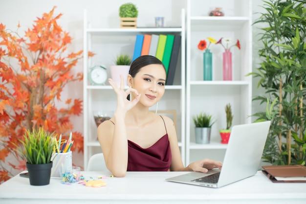 Señora alegre del negocio que trabaja en el ordenador portátil en oficina