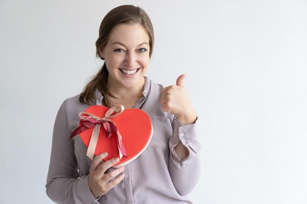 Señora alegre que muestra la caja y el pulgar en forma de corazón de regalo para arriba
