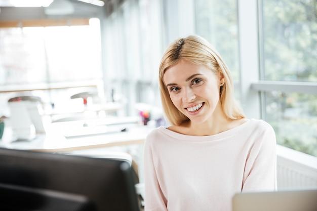 Señora alegre que se sienta en el coworking de la oficina usando la computadora.