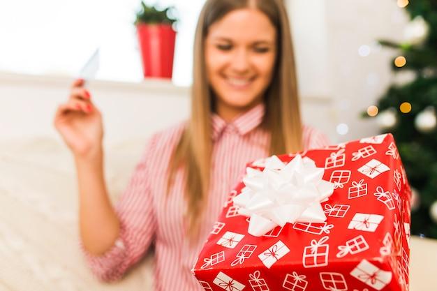Señora alegre que sostiene la caja de regalo y la tarjeta de crédito cerca del árbol de navidad