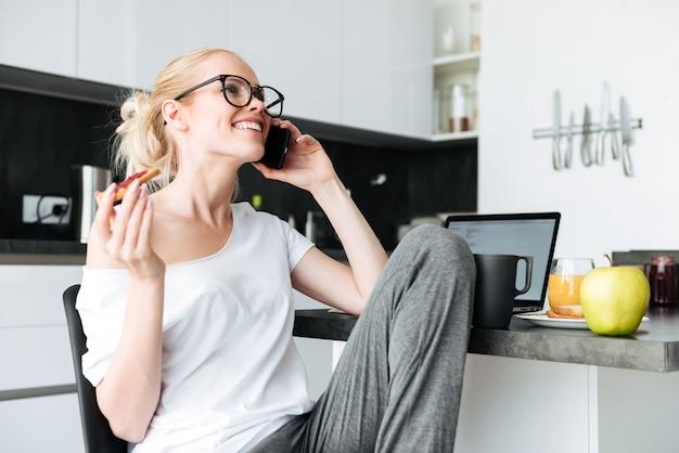 Señora alegre riendo mientras habla por teléfono inteligente en la cocina