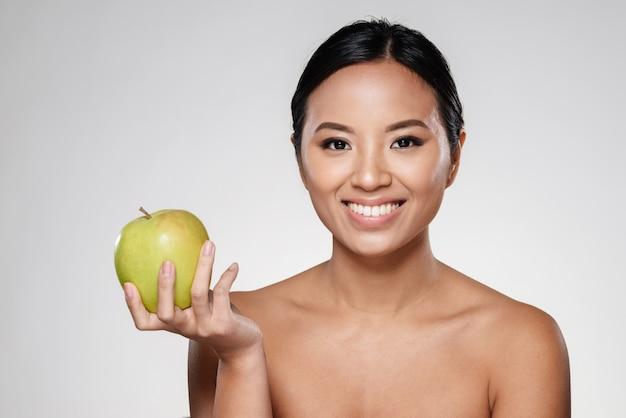 Señora alegre sonriendo y comiendo manzana verde